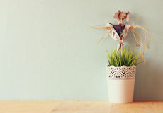 Vintage Flower pot and Scarecrow against mint wall and antique lace fabric Stock Photos