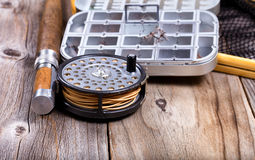 Vintage fly fishing reel and gear on rustic wooden background Royalty Free Stock Photos