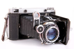 Vintage folding photocamera. Vintage reflex photocamera on white isolated on background in opened unfolded state royalty free stock photography