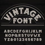 Vintage font. Dirty letters on a grunge wooden background. Vintage font. Retro alphabet. Dirty letters on a grunge wooden background. Vector typeface Royalty Free Stock Photo