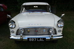 Vintage ford consul. White vintage ford consul car seen from front with three badges against dark background Stock Photo