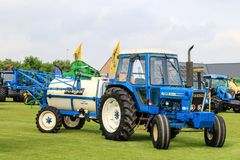 Old blue ford 7600 tractor pulling a knight crop sprayers at show Royalty Free Stock Image