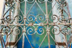 Vintage forged iron ornaments; colorful wall background, California stock photo