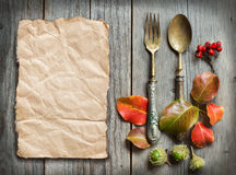 Vintage fork and knife with autumn leaves on wood Royalty Free Stock Photo