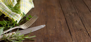 Vintage fork and knife with herbs and napkin. On an old wooden table Royalty Free Stock Images