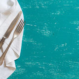 Vintage fork and knife on napkin on turquoise wood Royalty Free Stock Images