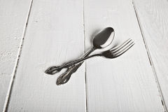 Vintage fork and spoon on white. Wooden table Stock Images