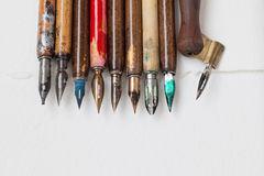 Vintage fountain pen collection. Aged colorful pens, textured white paper background. Artist tools concept. macro, up stock photo