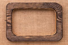 Vintage frame made of dark wood lying on burlap. With space for text. Stock Photography