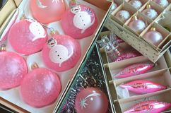 Vintage pink Christmas tree decorations in boxes piled on a table. Vintage frosted pink Christmas tree decorations in boxes piled on a table Royalty Free Stock Photo