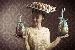 Vintage funny easter woman. Funny easter shoot of brunette female with yellow dress and bizarre hat with eggs in carton box . old fashion style Royalty Free Stock Photos