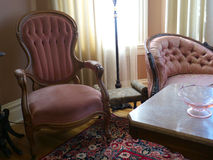 Vintage furniture, chair and love seat. Baroque chair and love seat and a marble top table in a nineteen century room. Persian carpet on the hardwood floor Royalty Free Stock Photos