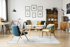 Vintage furniture in a flat. Stylish vintage furniture in a spacious flat interior with beige sofa, chairs and posters on the wall stock images