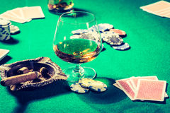 Vintage gambling table with whiskey, cigar and cards Royalty Free Stock Image