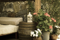 Vintage garden. A vintage photo of a garden with an old wooden bed, icon-lamp, flowers and an old wooden barrel Royalty Free Stock Photography