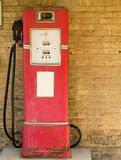 Vintage gas pump. Antique gas pump with white sticker against grungy brick wall Stock Photography