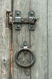 Vintage gate valves and old wooden gates with round metal handles in the form of rings. royalty free stock photos