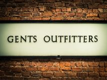 Vintage Gents Outfitters Sign. Old Fashioned Retro Vintage Gents Outfitters Sign On A Red Brick Wall In London stock photos