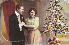 Vintage German christmas postcard. GERMANY- CIRCA 1910: Vintage christmas card with weathered edges printed in Germany in 1915 with loving couple beside a Stock Images