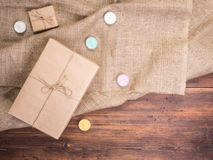 Vintage gift box, colored candles on old wood planks and burlap vintage background, photo top view. Copy space for text. Vintage gift box, colored candles on old Stock Image