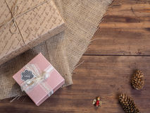 Vintage gift box, fir cones, Christmas toy on wood and burlap background, photo top view. Copy space for text. Stock Image