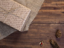 Vintage gift box, fir cones, Christmas toy on wood and burlap background, photo top view. Copy space for text. Stock Photo