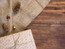 Vintage gift box, fir cones, Christmas toy on wood and burlap background, photo top view. Copy space for text. Stock Images