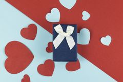 Vintage gift box and heap of hearts on multi colored background. Vintage gift box and heap of hearts on multi colored background Stock Photos