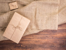 Vintage gift box on old wood planks and burlap vintage background, photo top view. Copy space for text. Top view, Studio. Vintage gift box on old wood planks and Stock Photos