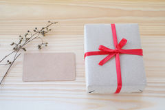 Vintage gift box with red ribbon bow and card on wood background Royalty Free Stock Photos