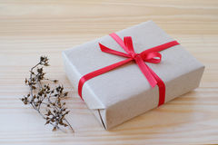 Vintage gift box with red ribbon bow on wood background Royalty Free Stock Photos