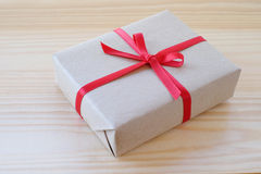 Vintage gift box with red ribbon bow on wood background Royalty Free Stock Photo