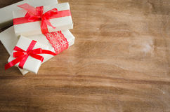 Vintage gift boxes with red bow ribbon on wooden background. Royalty Free Stock Image