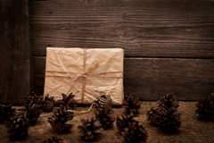 Vintage gift on wooden background with cones Royalty Free Stock Image
