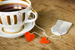Vintage gilded cup of black tea and heart  label Stock Photo