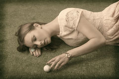 Vintage girl's lying on grass with golf ball Royalty Free Stock Images