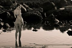 Vintage girl. Walking in the water looking you Royalty Free Stock Image