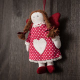 Vintage girl Christmas handmade toy. Hand made textile Girl Christmas decoration. Christmas toy. Vintage style, over wood background Royalty Free Stock Photography