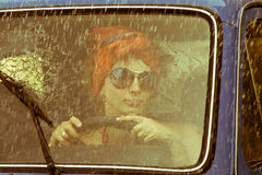 Vintage girl driving car. Under rain royalty free stock images
