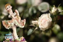 Vintage Girl Figurine wearing petticoat with Guitar and a white rose on creamy green background. Composition
