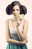 Vintage girl with lollipop, she looks the lollipop Stock Photos