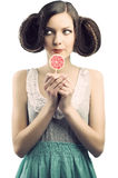 Vintage girl with lollipop, she looks at right Royalty Free Stock Photography