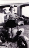 Vintage girl on old scooter. Girl portrait on a old scooter. The photo is taken in 1954. Photo with glamour glove filter royalty free stock image