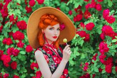 Vintage girl with red lips in dress with print of roses with red candy on summer garden. Redhead model in summer hat on background stock photo