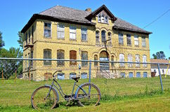 Vintage girls bike leans against a fence of a former old high school building Stock Photo