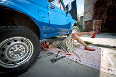 Vintage girl with tools under car Stock Photos