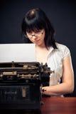 Vintage Girl With Typewriter. Photo of vintage girl working on a typewriter royalty free stock image