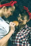 Vintage girlfriends, dressed in old-style feed of another girl Stock Photo