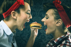 Vintage girlfriends in old style dress eat hamburgers Stock Photography