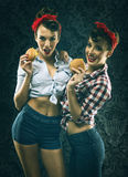Vintage girlfriends in old style dress eat hamburgers Royalty Free Stock Photos